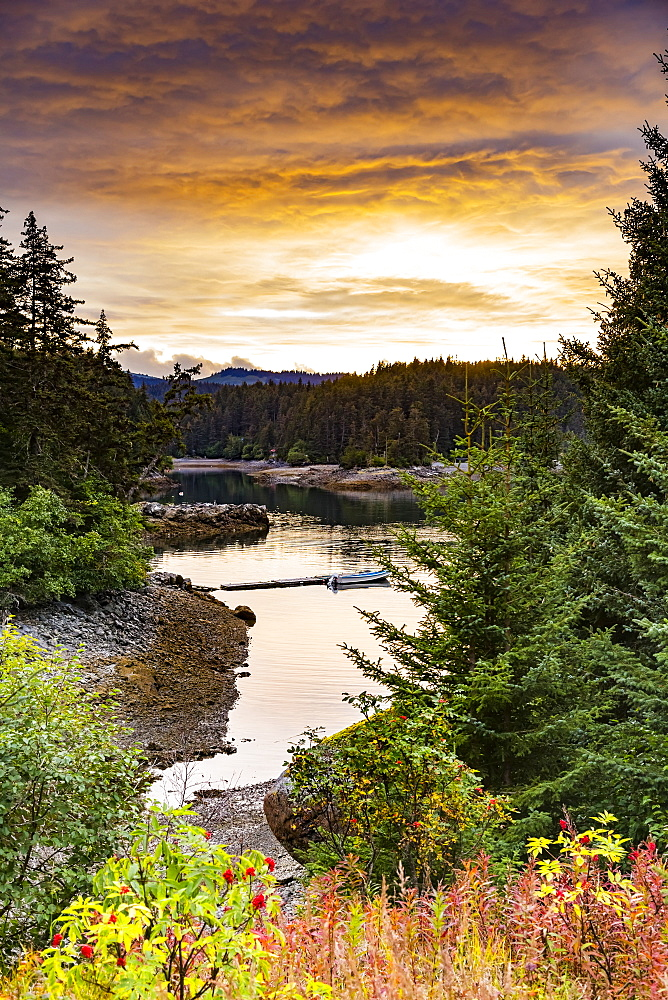 A scenic view of the coastline with forests and foliage in autumn colours and a small boat moored along a dock near Tutka Bay, on the southern end of Kachemak Bay, Homer, Alaska, United States of America