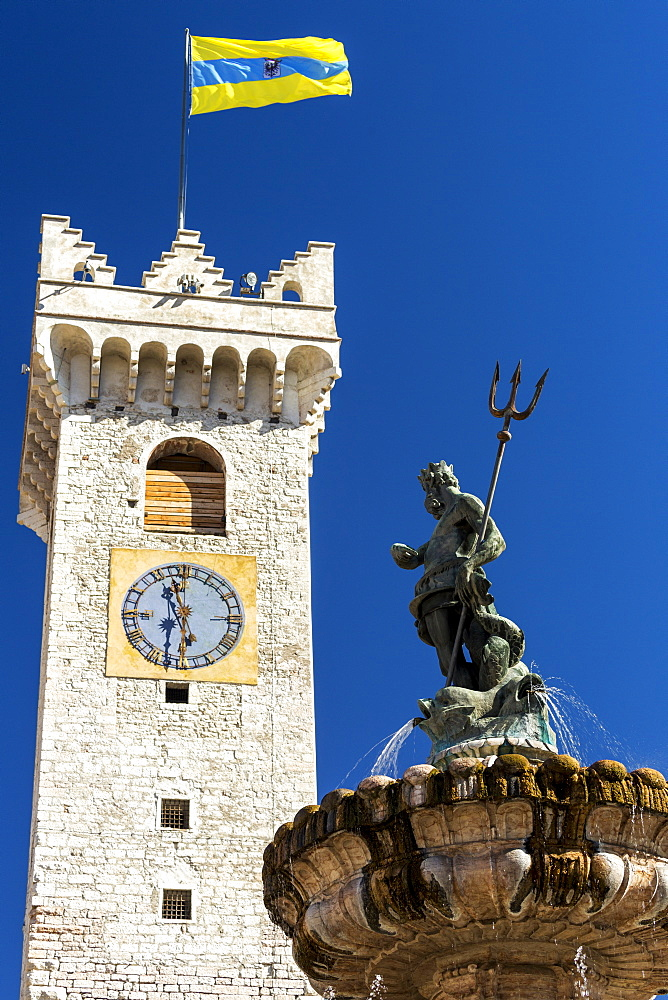 Fountain top of Poseidon with trident and large stone clock tower with flag of Trento in the background with blue sky, Trento, Trento, Italy