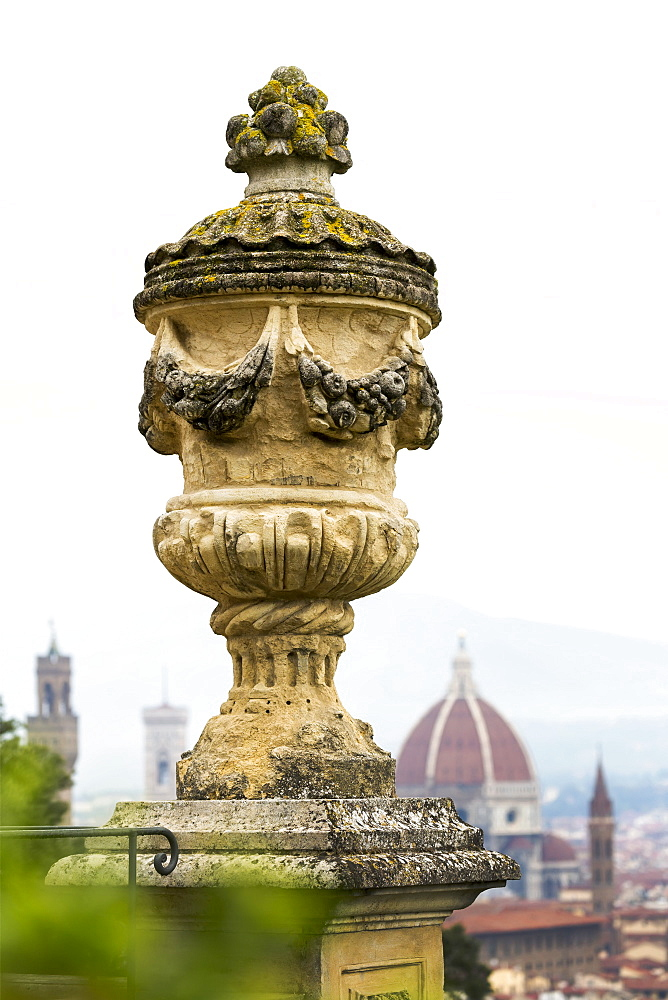Close-up of stone urn on top of column with dome of Florence Cathedral and towers in the background, Florence, Tuscany, Italy