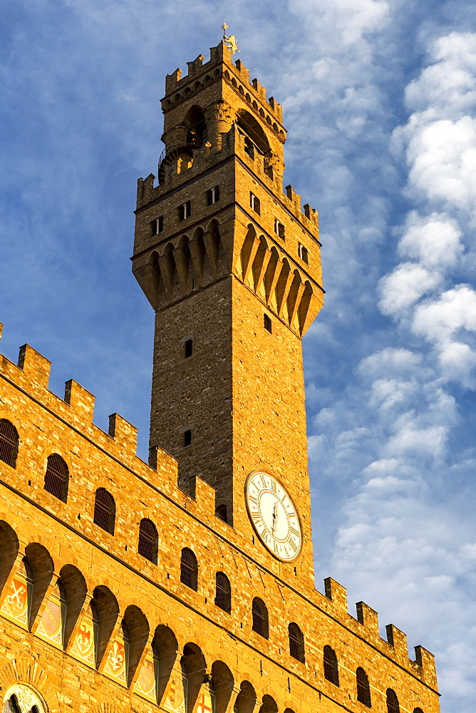 Large stone clock tower on top of castle walls with dramatic clouds and blue sky, Florence, Tuscany, Italy