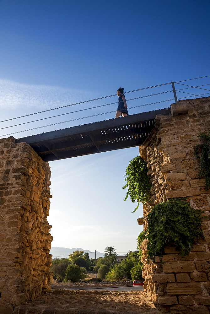 Tourist walking over the city wall, Alcudia, Mallorca, Balearic Islands, Spain