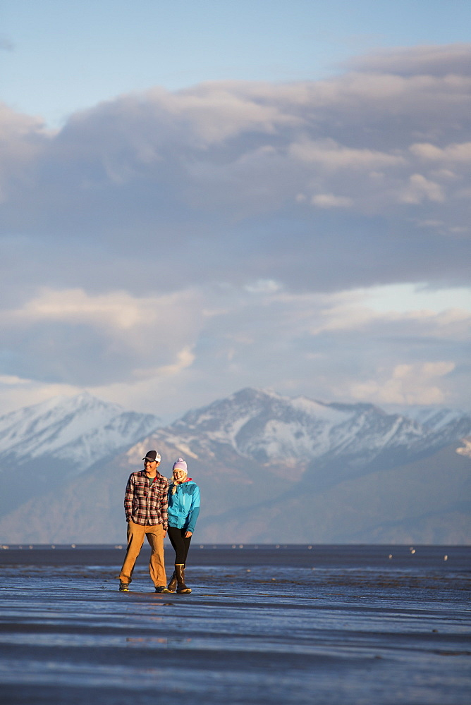 A young couple walking on a beach and holding hands with a mountain range in the distance, Anchorage, Alaska, United States of America
