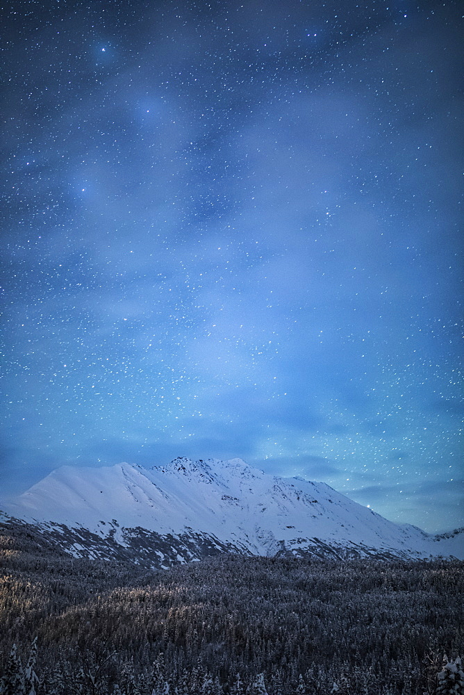 The faint glow of Aurora Borealis in the night sky illuminates the sparse cloud over Moose Pass, Kenai Peninsula, South-central Alaska, Moose Pass, Alaska, United States of America