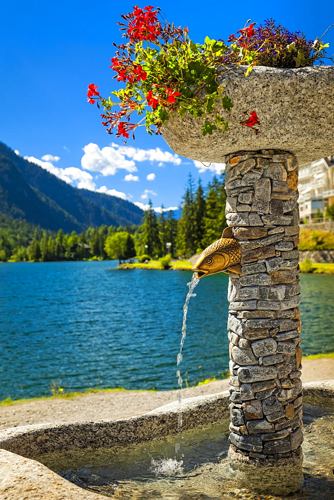 Close-up of a stone fountain with flower pots by Champex Lake and mountain range in the background, Champex, Valais, Switzerland