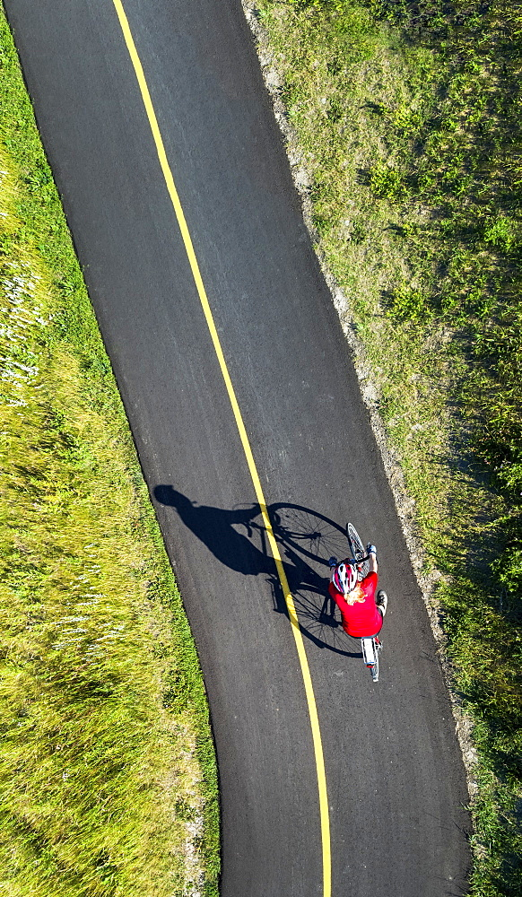 View from directly above a cyclist in a red shirt on a paved cycling trail, Calgary, Alberta, Canada