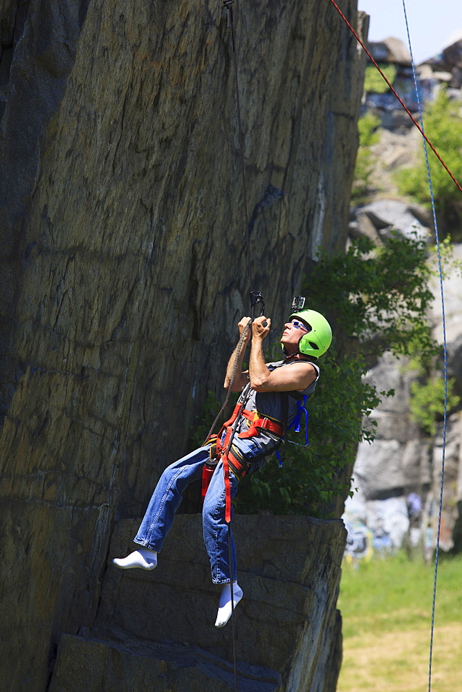Man with spinal cord injury using adaptive climbing equipment for rock climbing