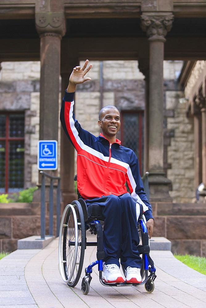 Man in wheelchair who had Spinal Meningitis using a ramp and waving