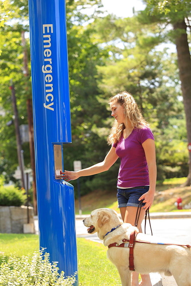 Student with visual impairment and her service dog using Emergency station at school