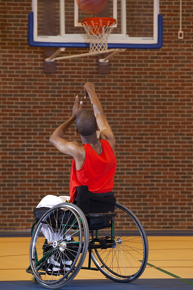 Man who had Spinal Meningitis in wheelchair taking a net shot in basketball