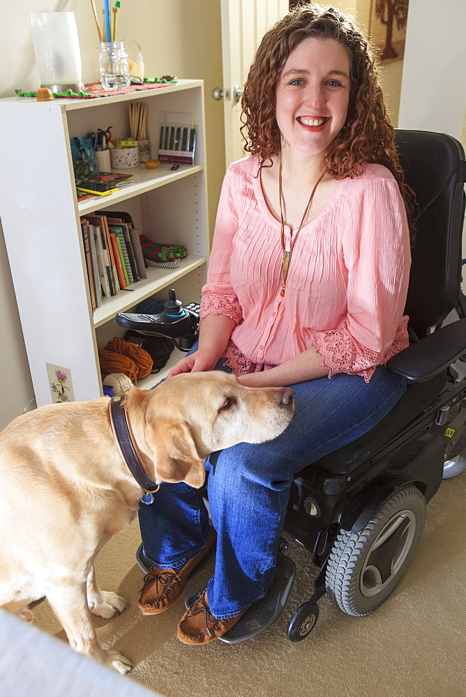 Woman with Muscular Dystrophy patting her service dog in her office