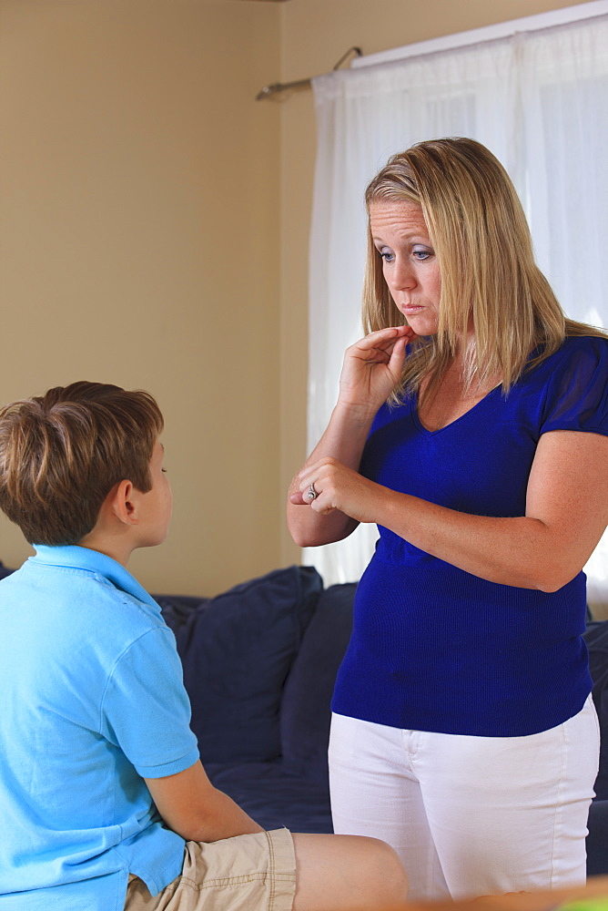 Mother and son with hearing impairments signing 'homework' in American sign language