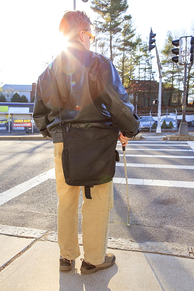 Man with congenital blindness about to cross the street using his cane