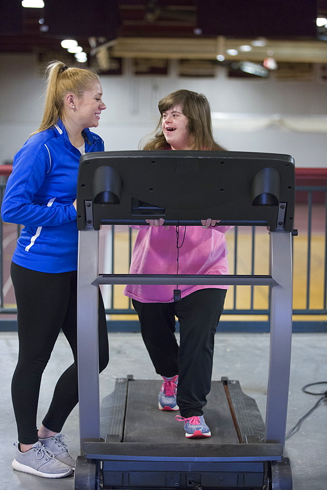 Young woman with Down Syndrome working out with her trainer on an exercise machine in gym