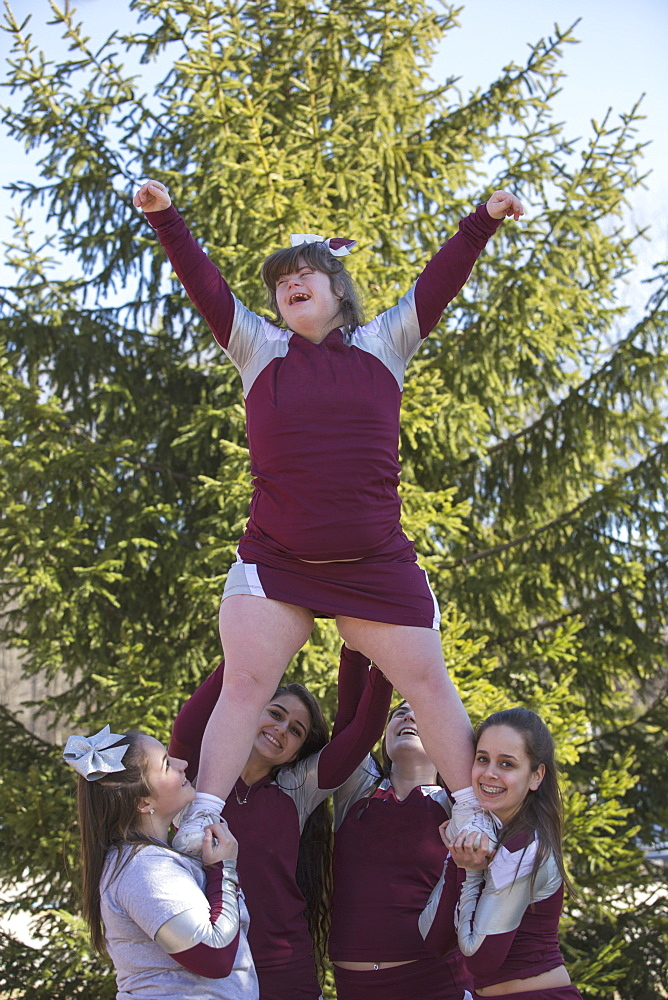 Cheerleaders lifting a cheerleader with Down Syndrome in the air
