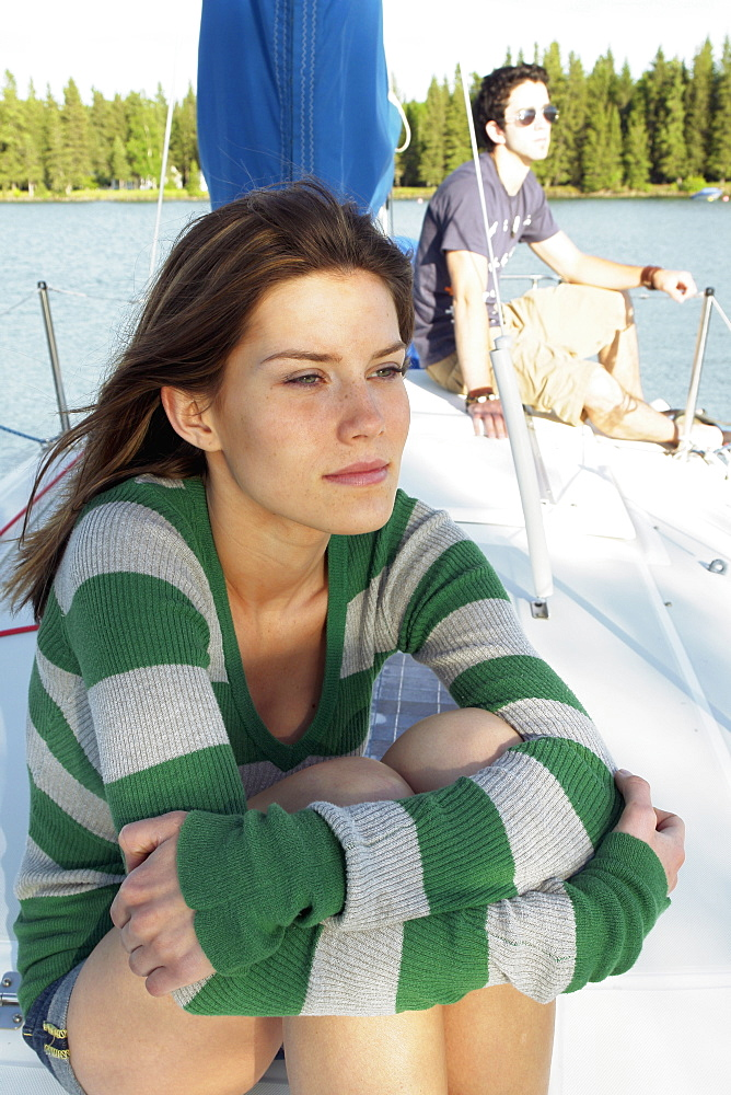 Young Woman In Foreground, Young Man In Background, On Sailboat, Clear Lake, Riding Mountain National Park, Manitoba, Canada