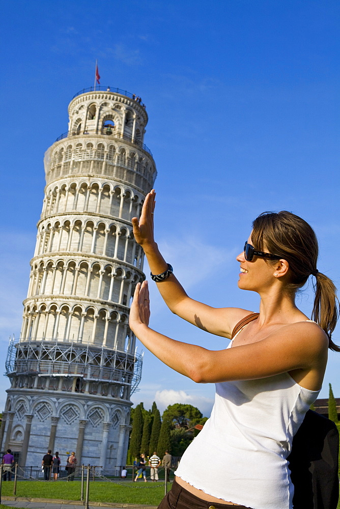 Young woman posing for photo with the Leaning Tower of Pisa, Pisa, UNESCO World Heritage Site, Tuscany, Italy, Europe