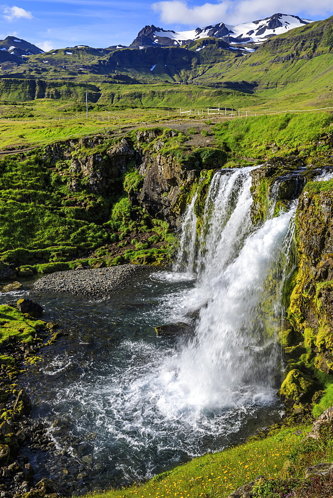 Kirkjufellsfoss Waterfall, snowy mountains, Grundarfjordur, blue sky, good Summer weather, Snaefellsnes Peninsula, Iceland