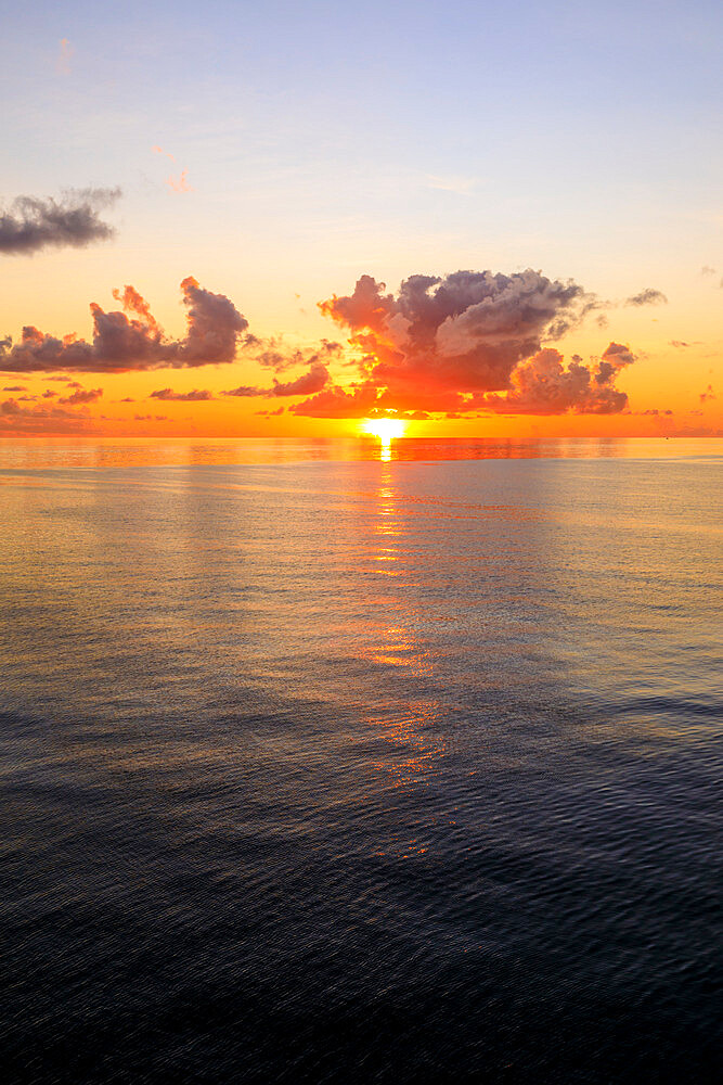 Sunset over beautiful calm sea, interesting clouds, vibrant colours, St. Kitts, St. Kitts and Nevis, Caribbean