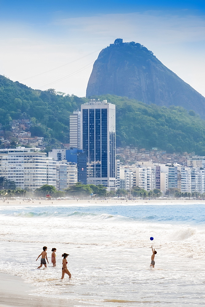 Brazil, Rio de Janeiro, Copacabana beach. Locals playing ball in the surf