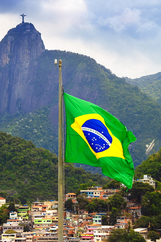 Brazilian flag with a favela and the Christ statue on Corcovado peak in the background, Rio de Janeiro, Brazil, South America
