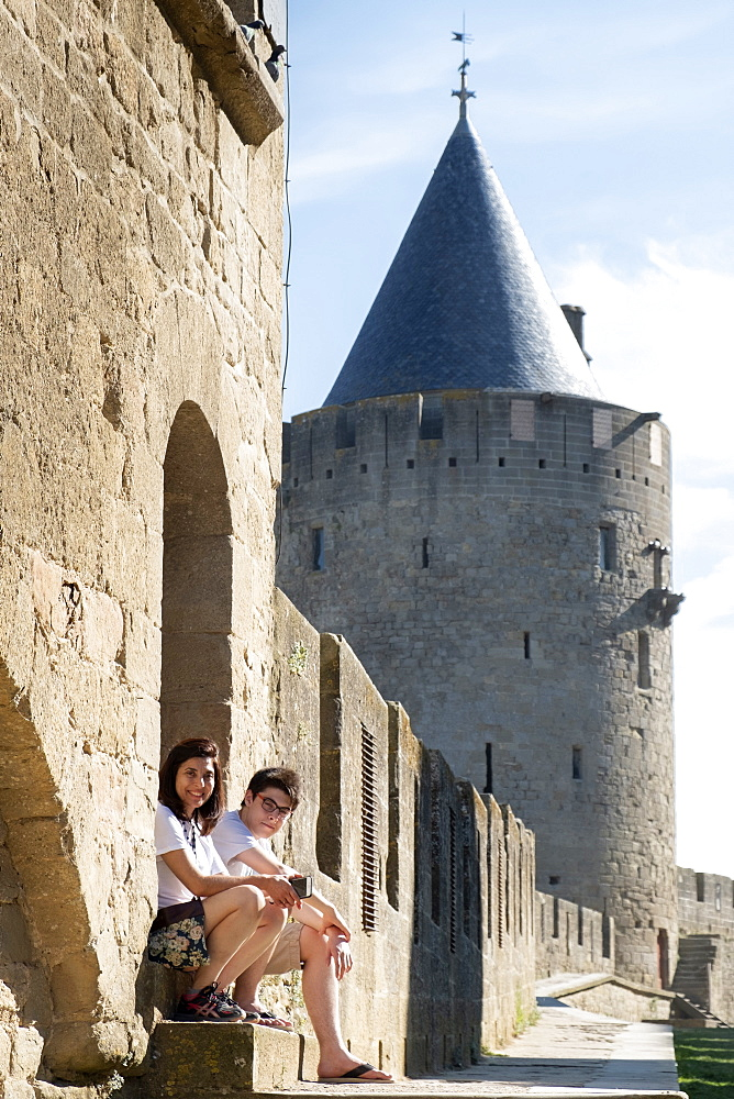 France, Carcassonne, Languedoc, Aude. A mother and son on holiday and seated outside the main wall of the medieval castle