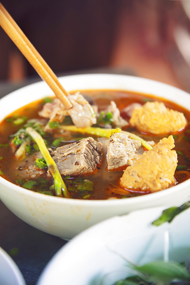 Vietnam, Hue. A steaming dish of Bun Bo Hue: the spicy local beef broth or hotpot, in a local restaurant