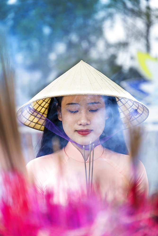 A young Vietnamese woman in a conical hat making incense offerings at a Buddhist temple, Hue, Vietnam, Indochina, Southeast Asia, Asia - 1176-1180