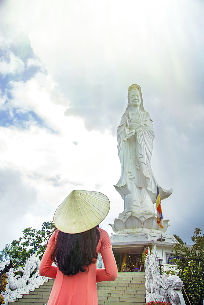 A young Vietnamese woman in a conical hat paying homage to Quan Am (Guanyin) at a Buddhist temple, Hue, Vietnam, Indochina, Southeast Asia, Asia