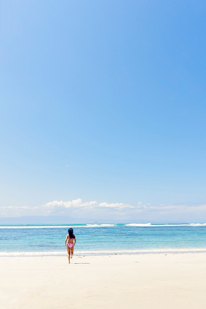 A young woman running into the ocean on a pristine tropical beach