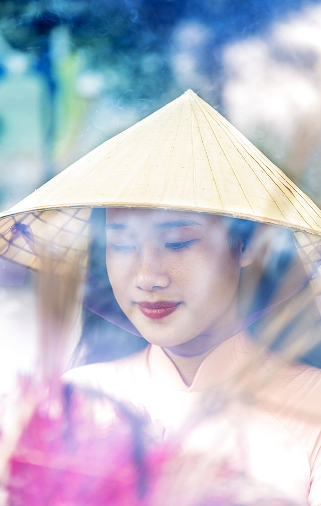 A young Vietnamese woman in a conical hat making incense offerings at a Buddhist temple, Hue, Vietnam, Indochina, Southeast Asia, Asia