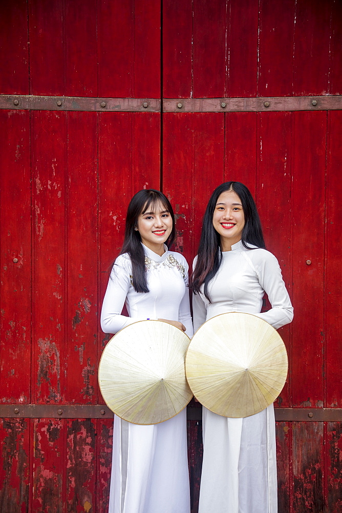 Vietnam, Hue. Two young women in traditional dress standing at the Western gateway to the Forbidden Purple City