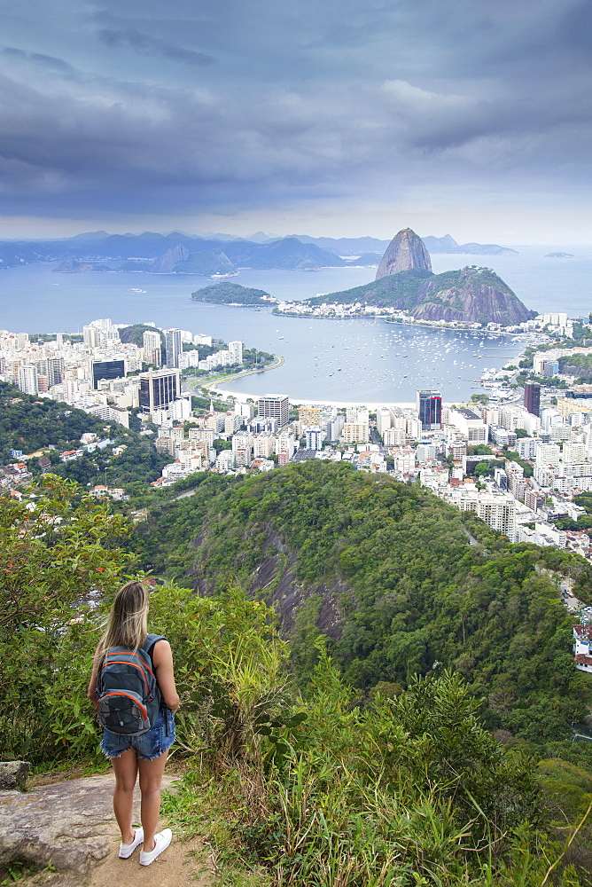 A female hiker looking out over the landscape of Rio to Sugar Loaf mountain from Tijuca National Park, Rio de Janeiro, Brazil, South America