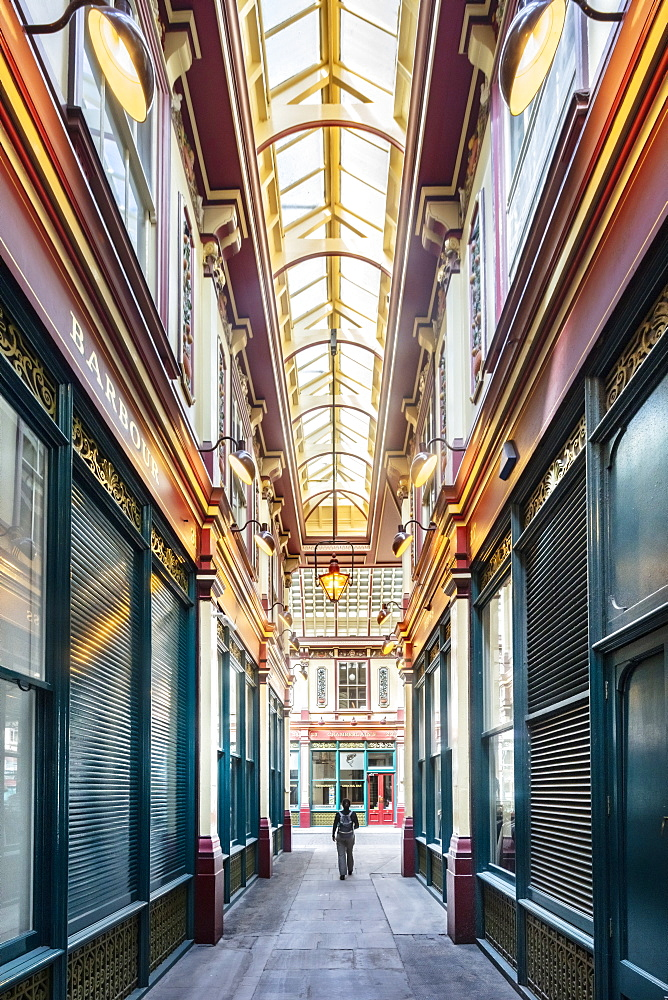 A woman walking through Leadenhall Market, a Victorian market designed by Horace Jones, City of London, London, England, United Kingdom, Europe