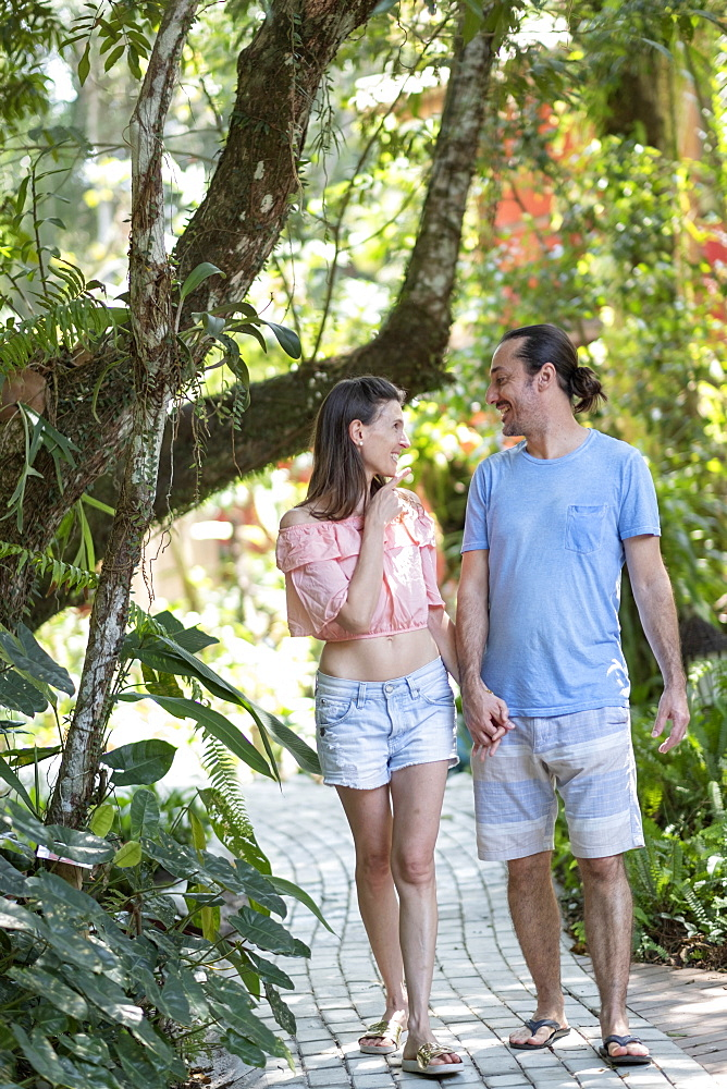 Brazil, Travel Lifestyle, a middle-aged couple happy together on a trail in a tropical forest or hotel garden