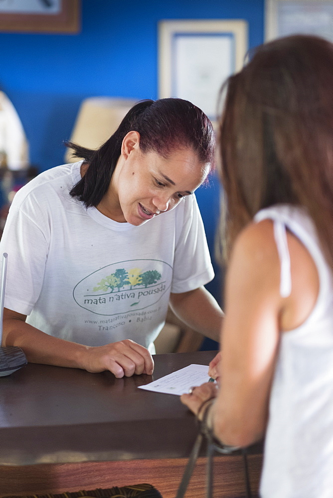 A woman checking-in to a hotel in Bahia, Trancoso, Bahia, Brazil, South America