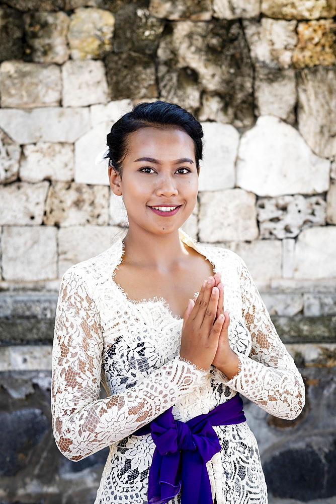 A young Balinese woman in a local temple dress making a formal greeting and smiling, Bali, Indonesia, Southeast Asia, Asia