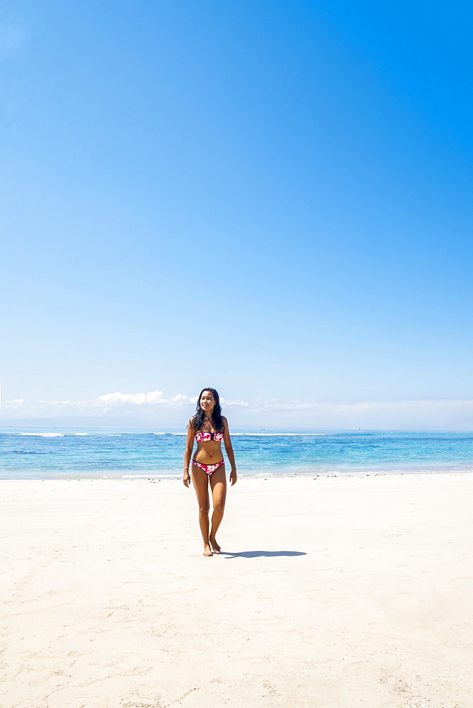 A beautiful Asian woman solo traveller in a bikini on a pristine tropical beach, Bali, Indonesia, Southeast Asia, Asia