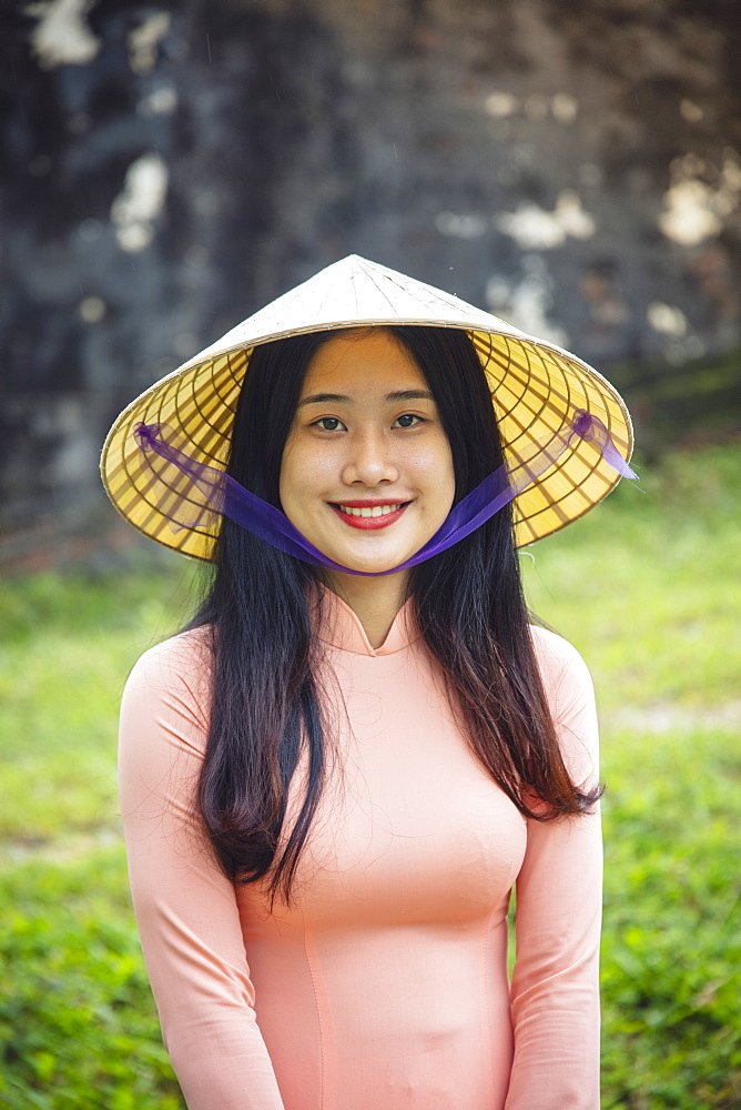 Vietnam, Hue. A young Vietnamese woman in a traditional Ao Dai dress and conical hat and smiling - 1176-1250