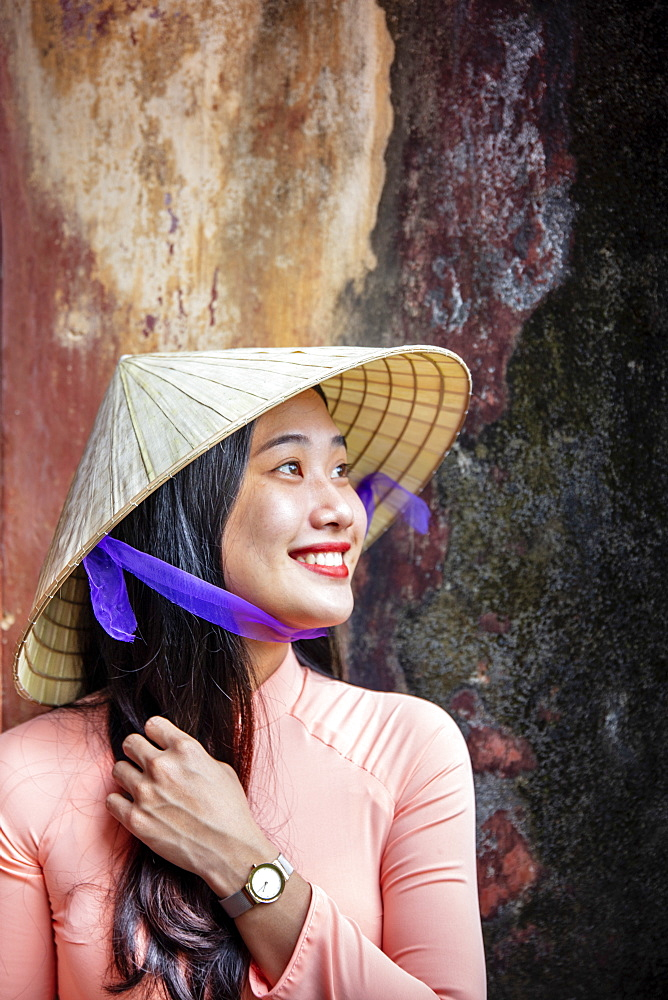 Vietnam, Hue. A young Vietnamese woman in a traditional Ao Dai dress and conical hat and smiling - 1176-1251