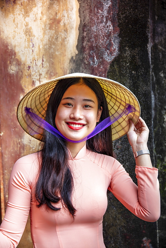 Vietnam, Hue. A young Vietnamese woman in a traditional Ao Dai dress and conical hat and smiling - 1176-1252