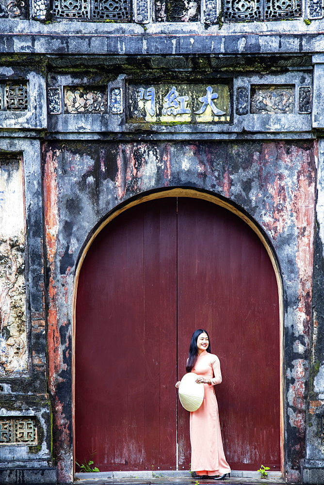 Vietnam, Hue. A young Vietnamese woman in a traditional Ao Dai dress and hat standing at the gateway to the Imperial Purple City - 1176-1253
