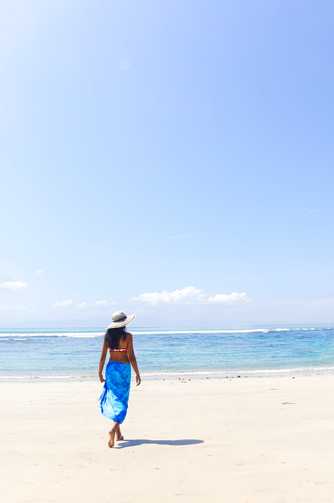 A young woman in a sunhat and shawl walking along a pristine tropical beach on Bali island