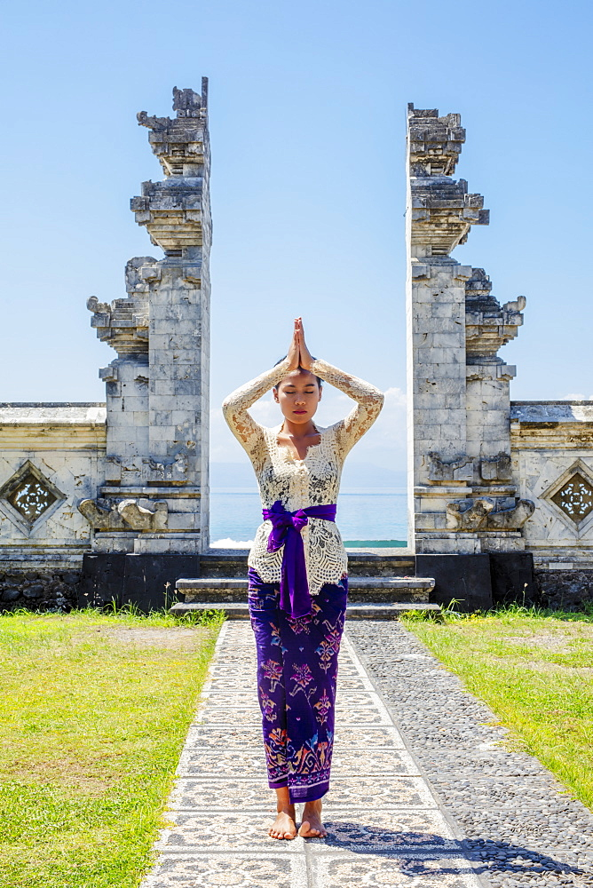 A young Balinese woman in traditional temple at the shoreside Pura Candidasa Hindu temple, Bali, Indonesia, Southeast Asia, Asia