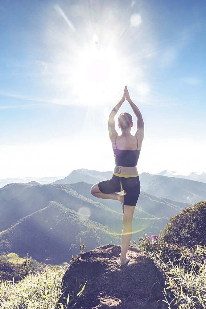 A young woman standing on a mountaintop in the rainforest, in a yoga pose, photographed against sunlight, Brazil, South America