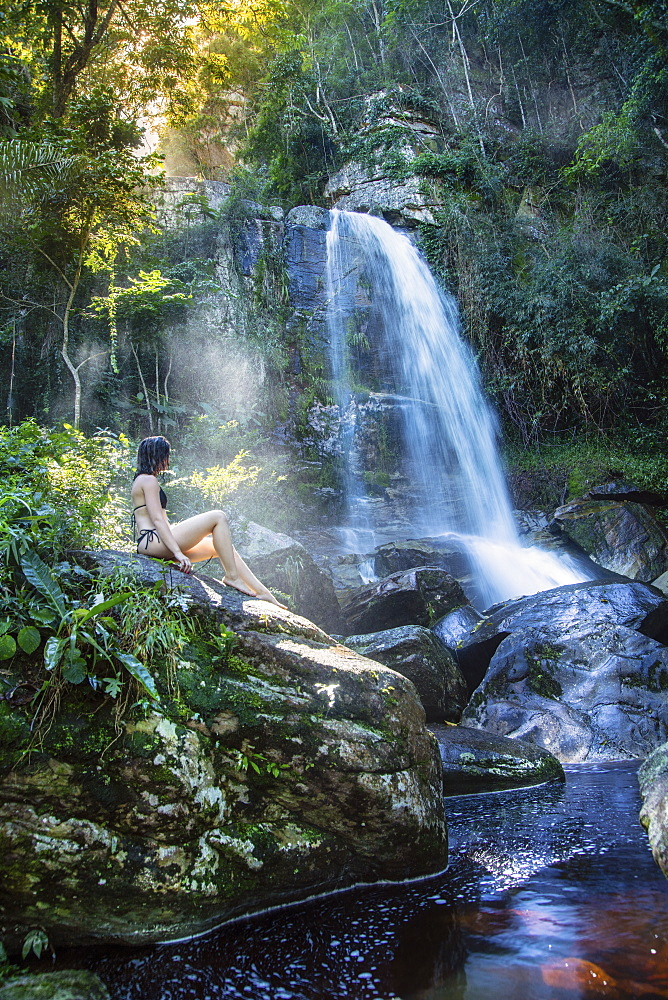 A beautiful young woman sitting in a shaft of sunlight in front of a pristine waterfall in the rainforest, Brazil, South America