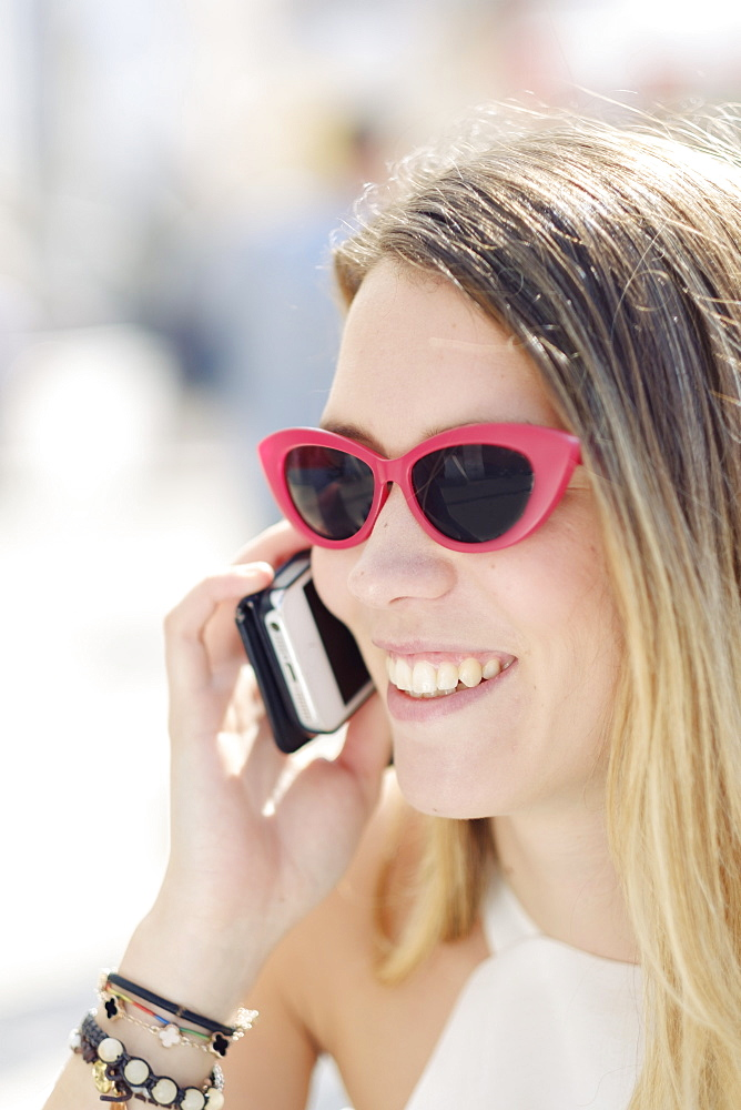 Headshot of a smiling young woman in sunglasses using her mobile phone outdoors, Portugal, Europe