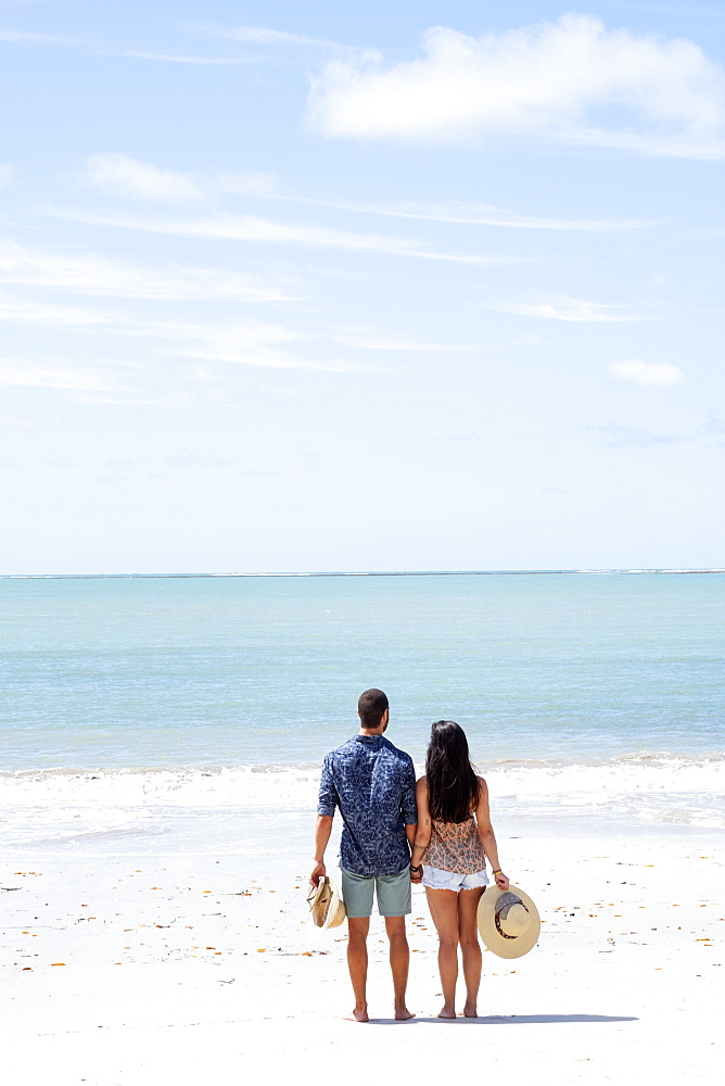 A good-looking Hispanic / Latin couple on a deserted beach with backs to camera and with copy space