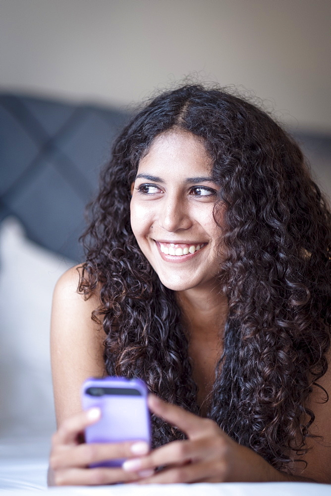 A Latin American woman lying on her bed with her mobile phone and smiling as she looks off camera, Brazil, South America