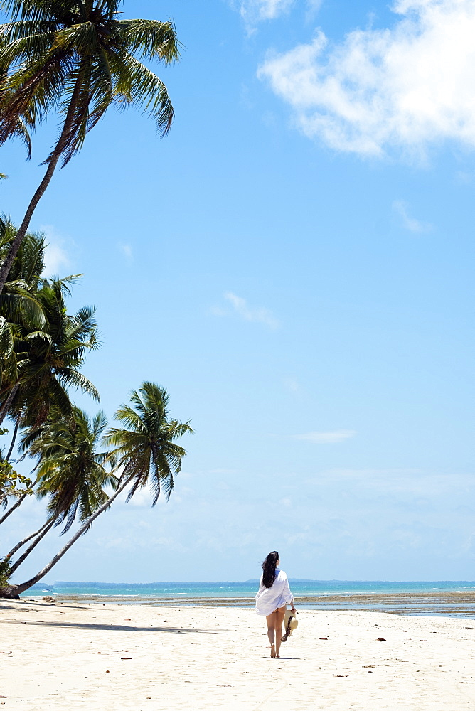 A young woman with brown hair wearing a white beach shirt and holding a hat walking along a tropical beach. Copy space.
