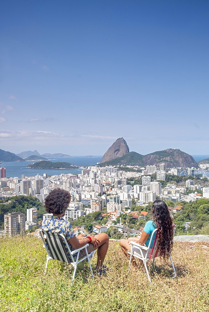 A multi-ethnic couple sitting together and looking out over Sugar Loaf mountain and the Rio skyline, Rio de Janeiro, Brazil, South America
